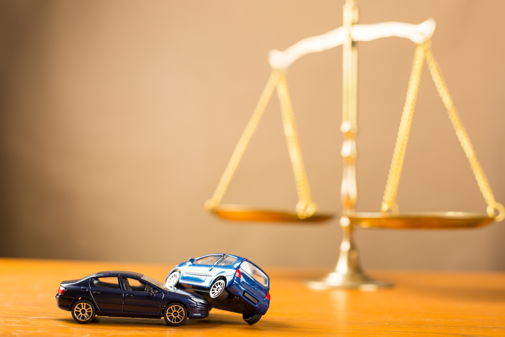 toy car crash in front of scales of justice