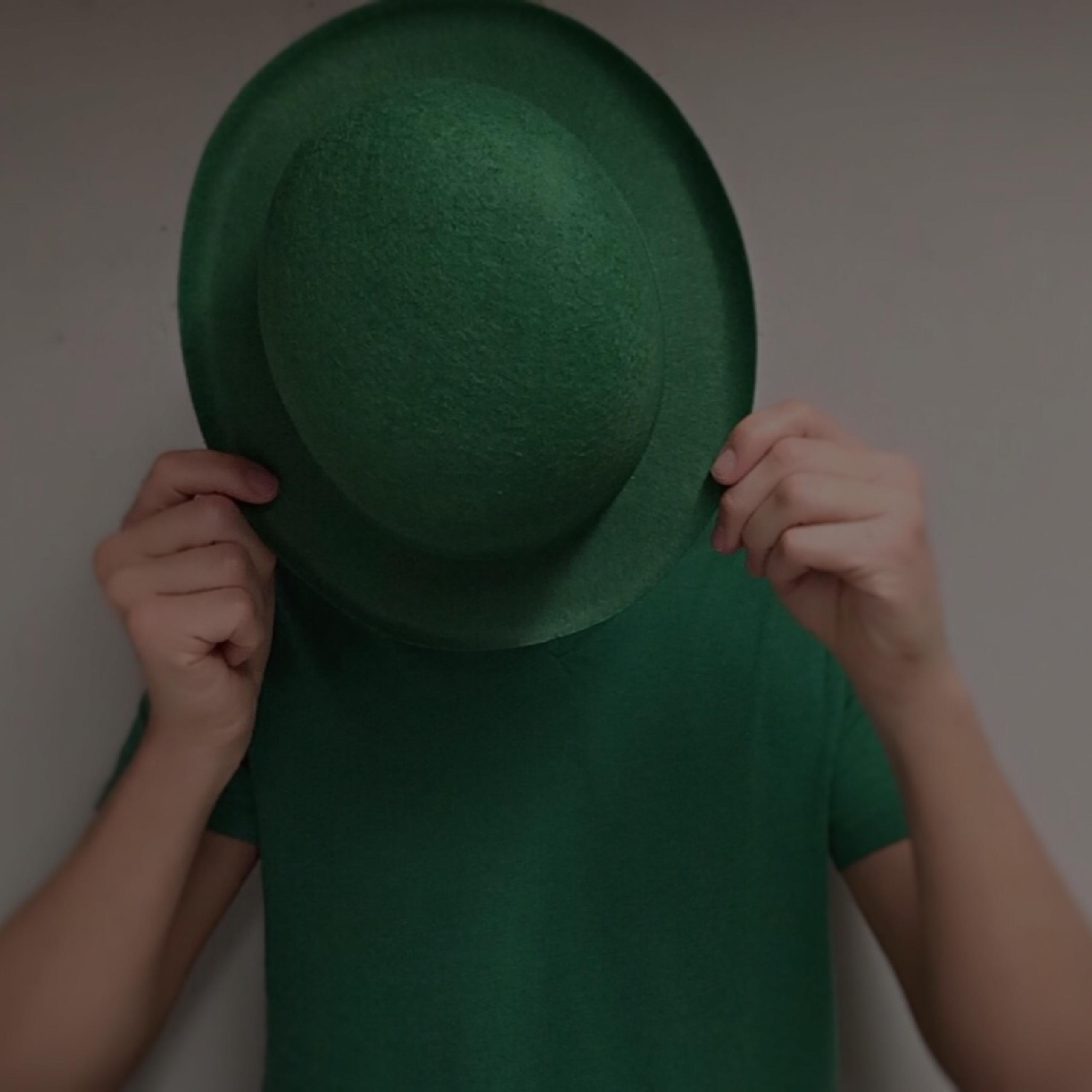 man in green shirt hiding behind green bowler hat on St. Patrick's Day