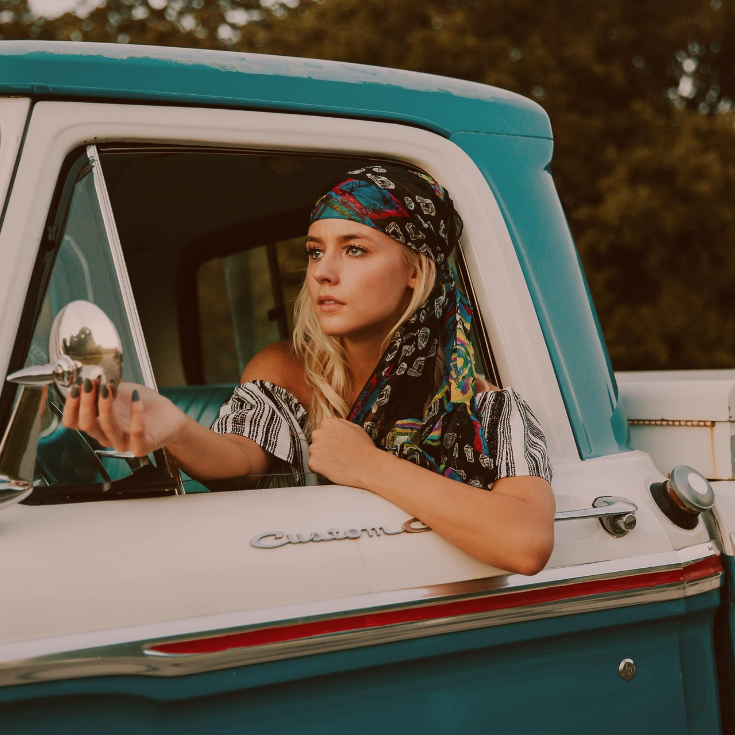 young girl in vintage pickup truck driver seat adjusting side view mirror