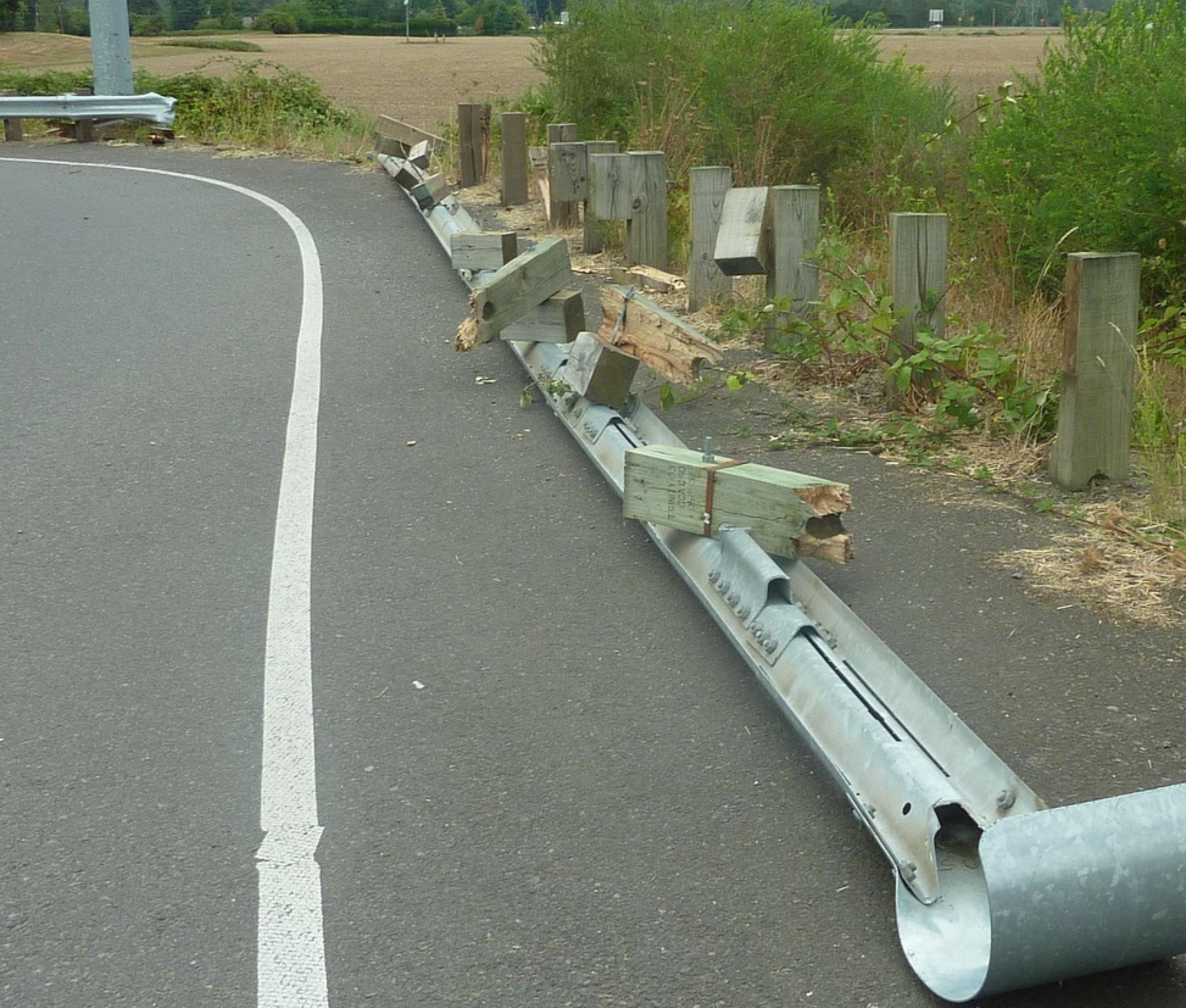 damaged guardrail on side of road after car accident
