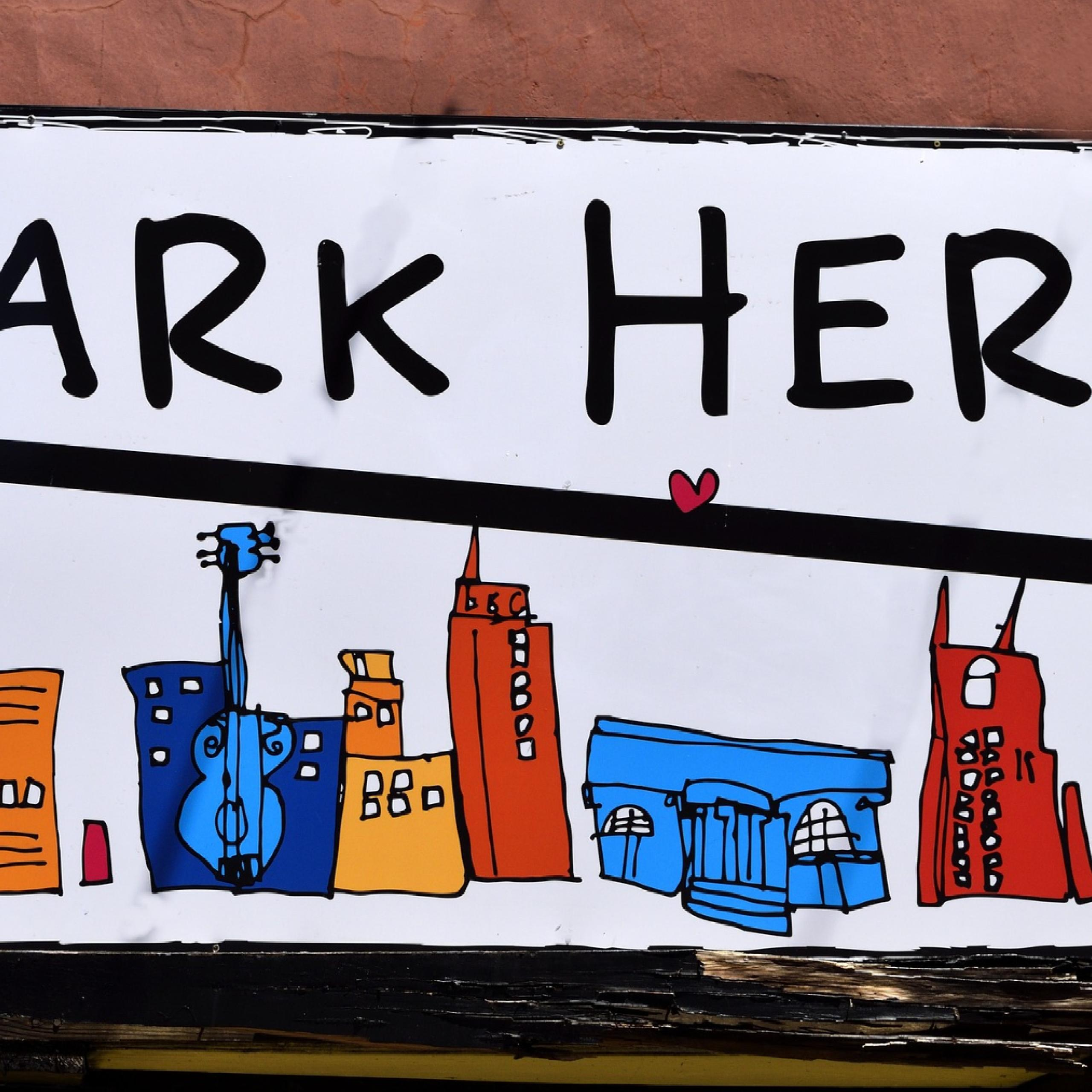 close up of park here sign with city drawings