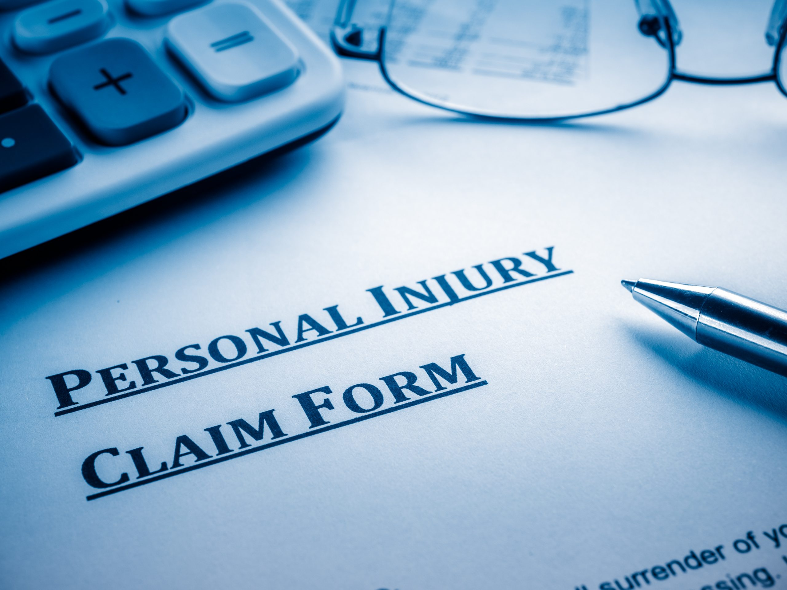 personal injury claim form with pen, glasses and calculator