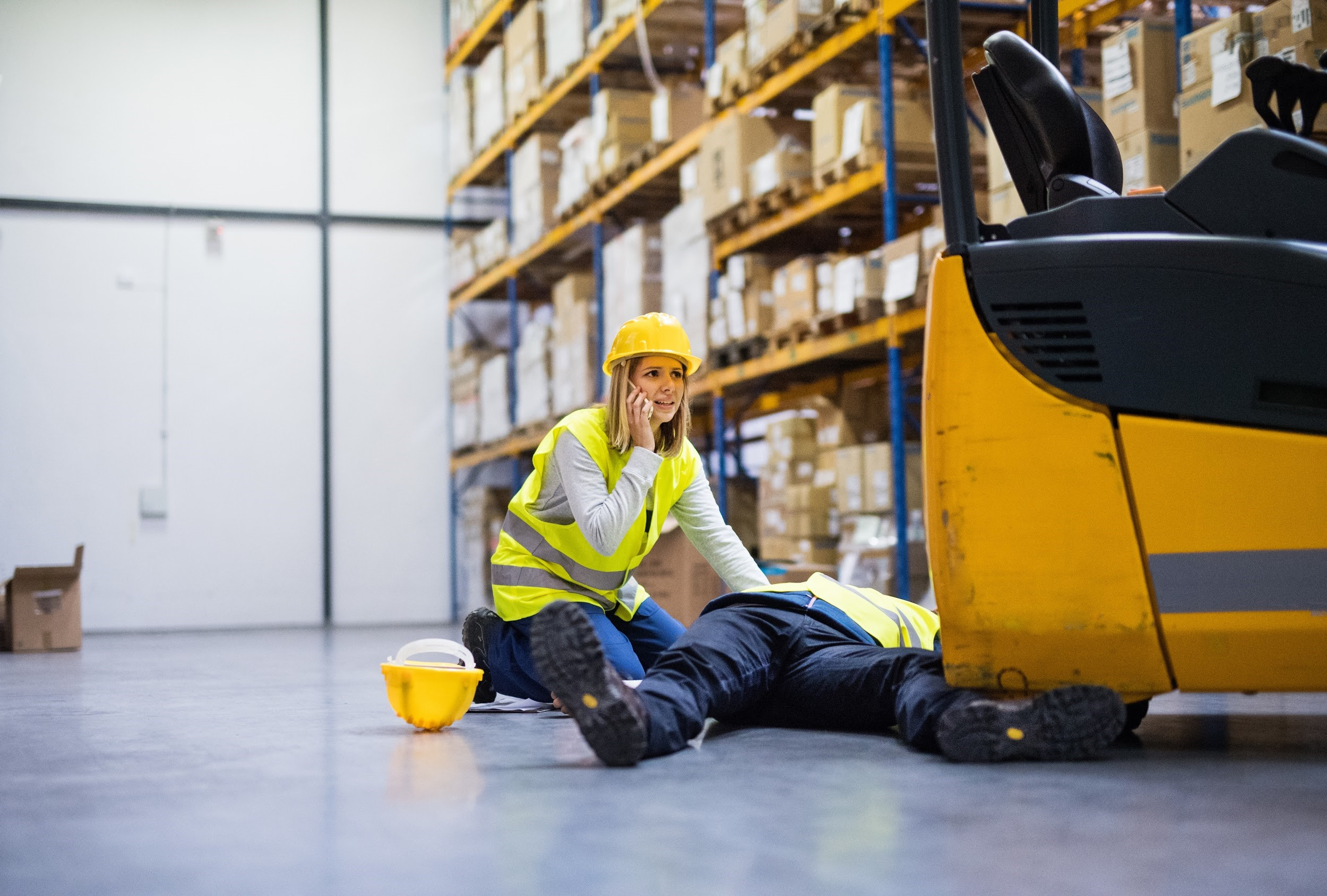 man laying on ground while coworker calls for help after forklift accident in warehouse