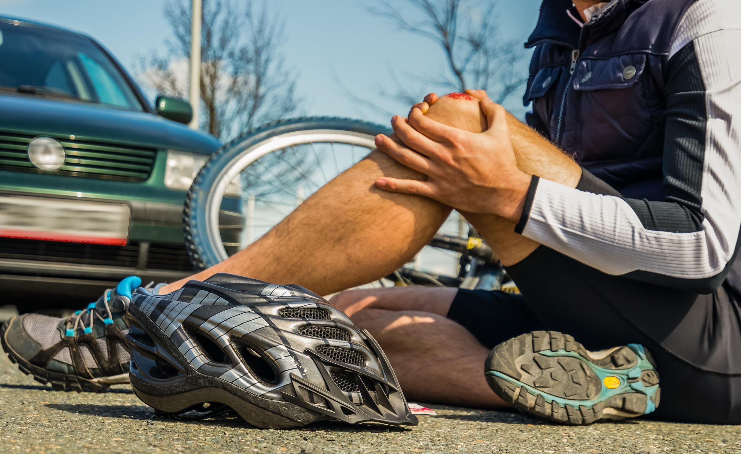 injured cyclist sitting on ground with bloody knee after accident