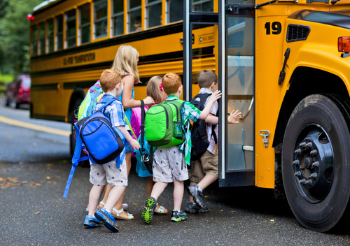 group of five students getting on school bus