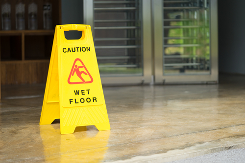 caution wet floor sign in commercial building before exit