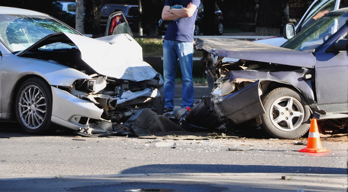 driver looking at car damage after head-on collision vehicle accident