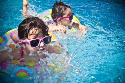 two young girls with sunglasses and tubes swimming in swimming pool