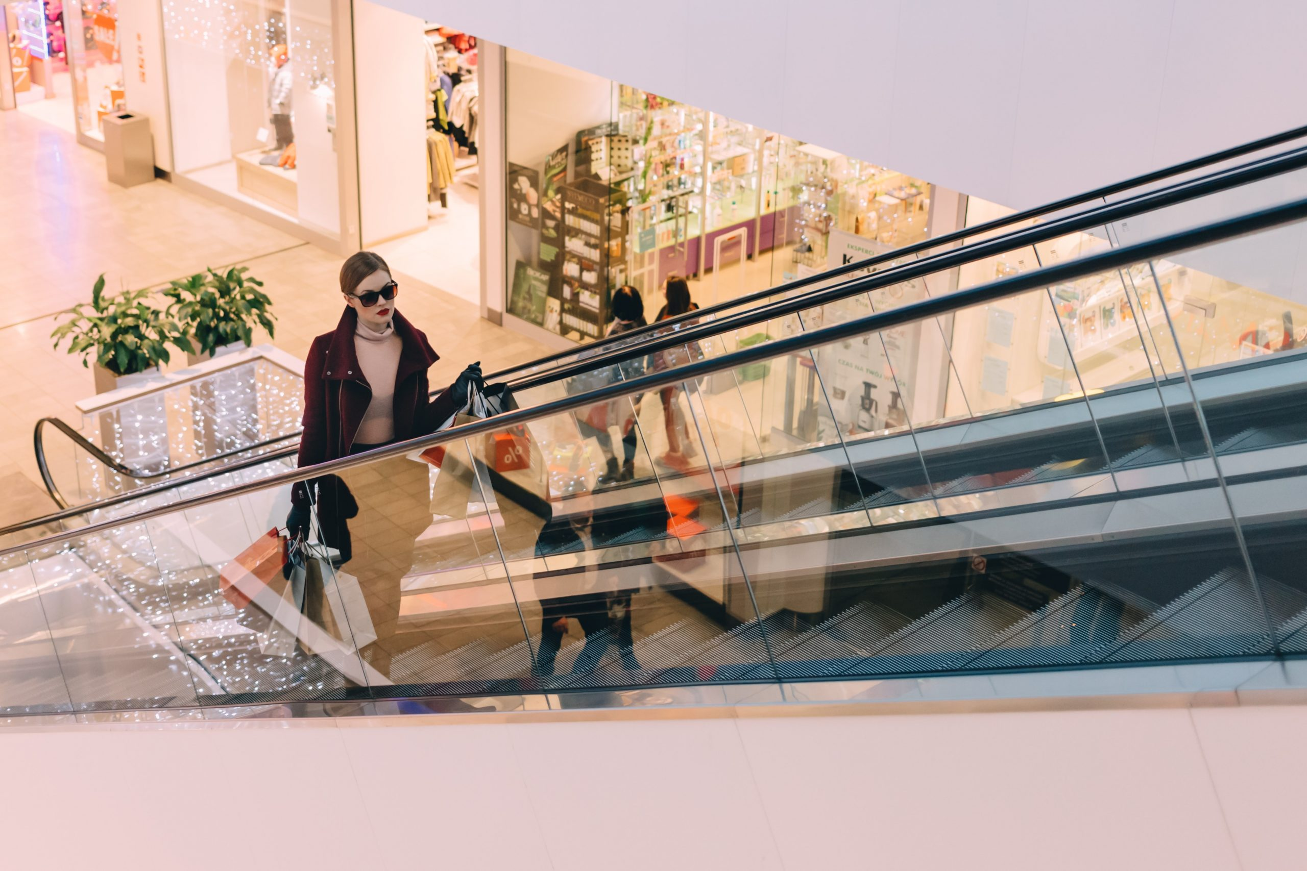 woman with shopping bags going up escalator in shopping mall