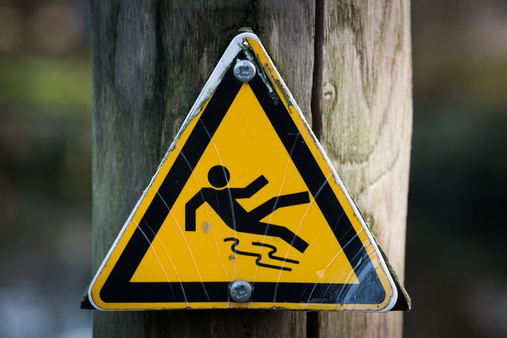 slippery warning sign on wooden post