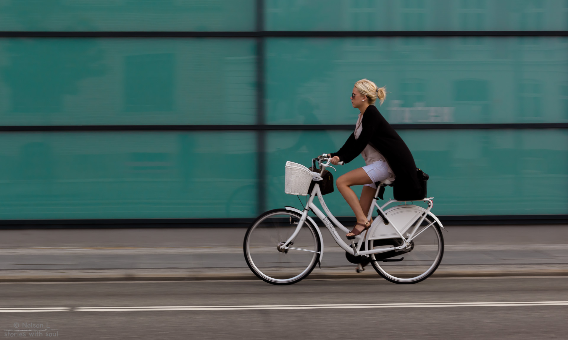 blond woman biking on white bicycle past big glass windows in city
