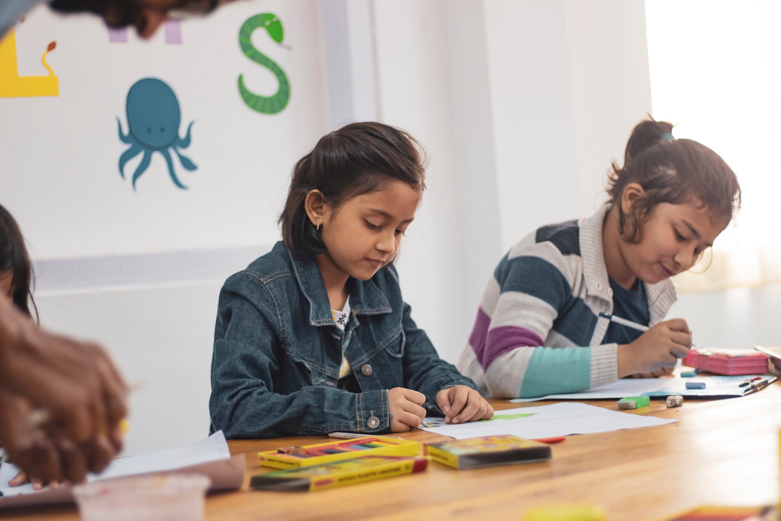children coloring in class at school