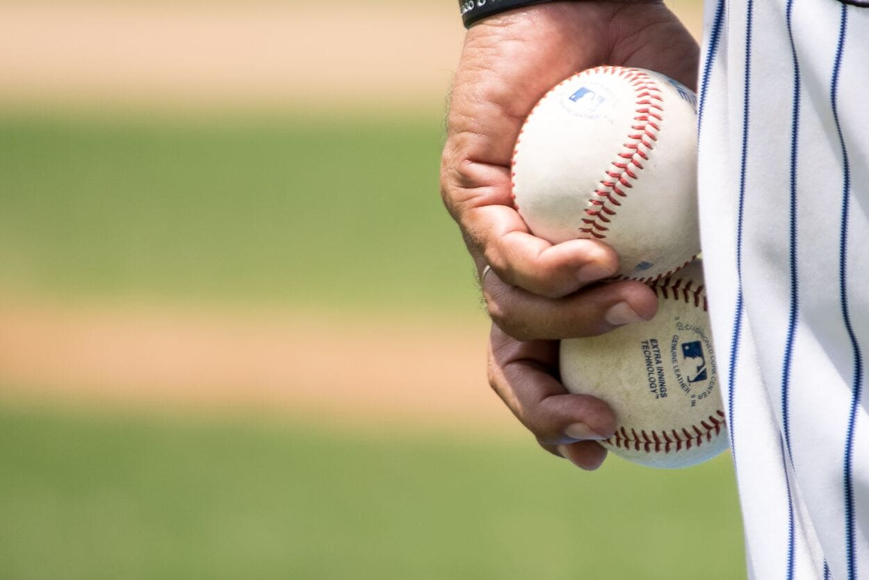 close up of baseball pitcher's hand with two baseballs
