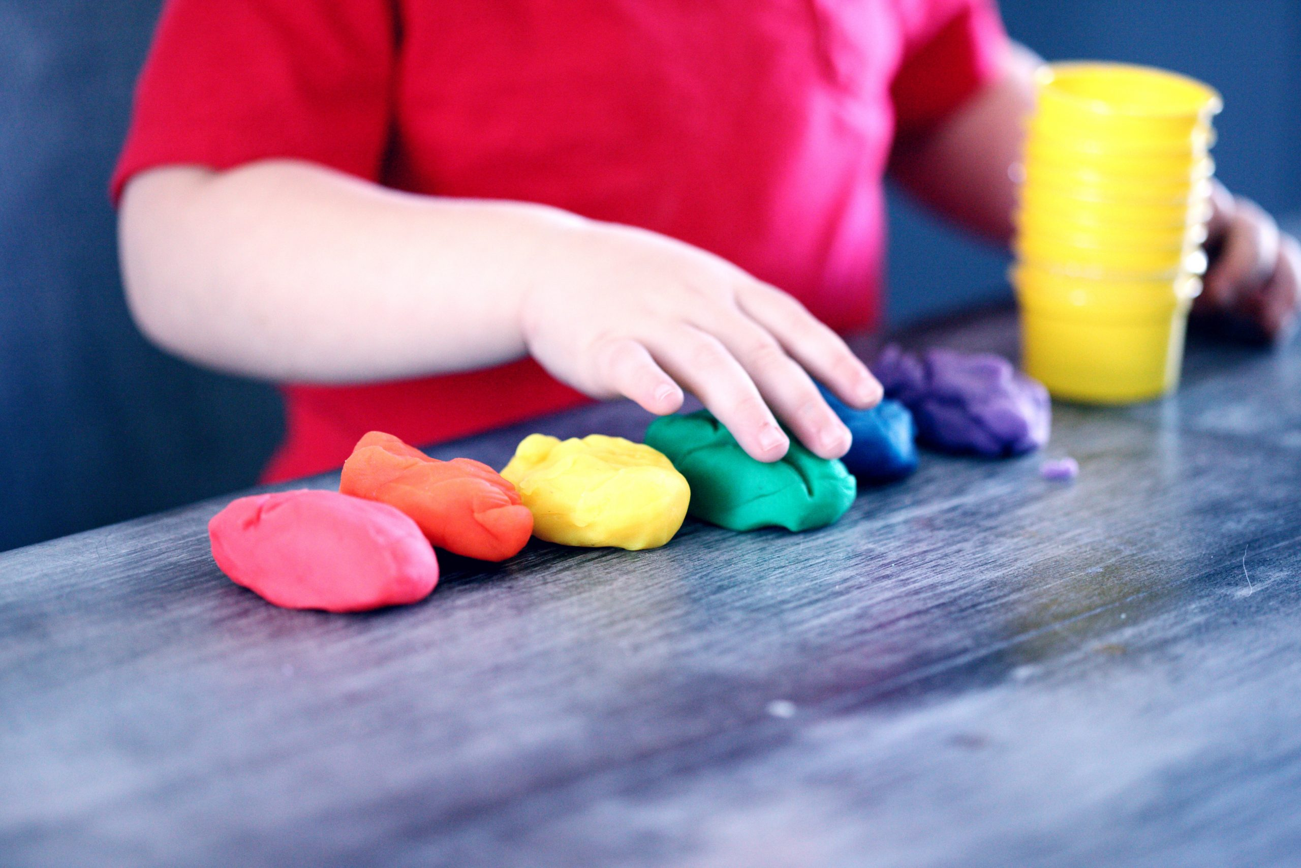 child playing with different colors of clay