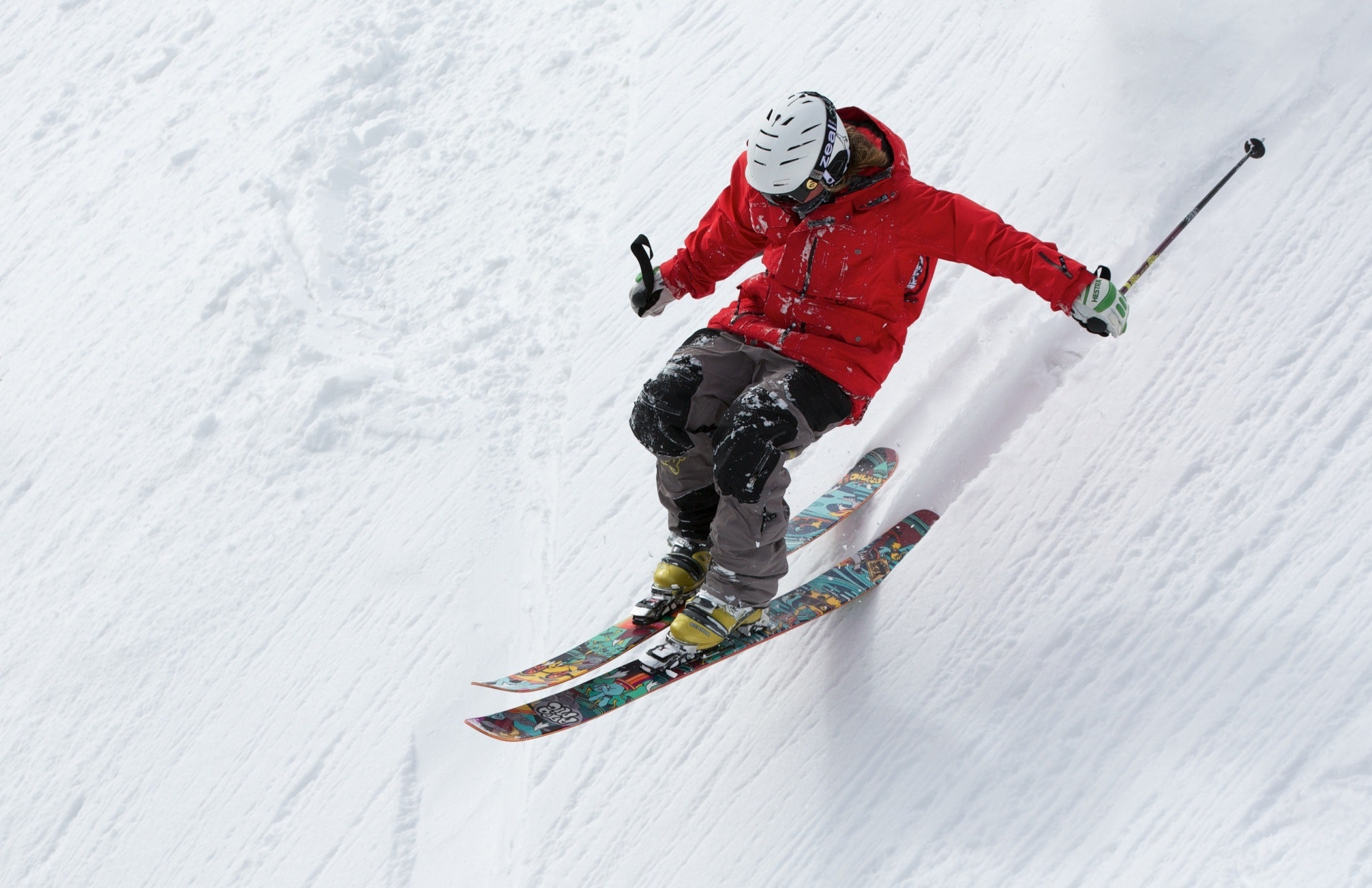 man in red jacket skiing down slope