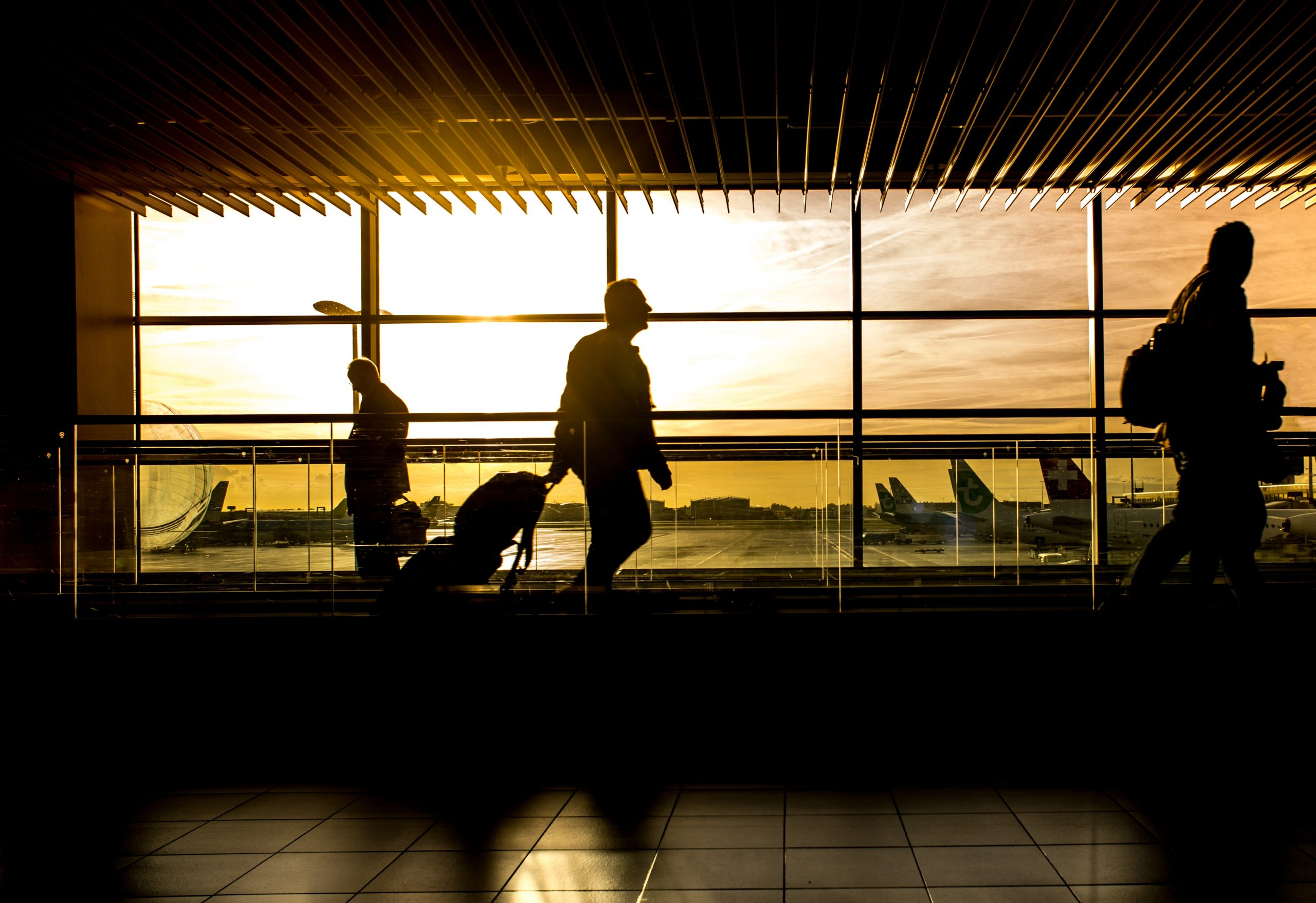 silhouettes of passengers walking through airport