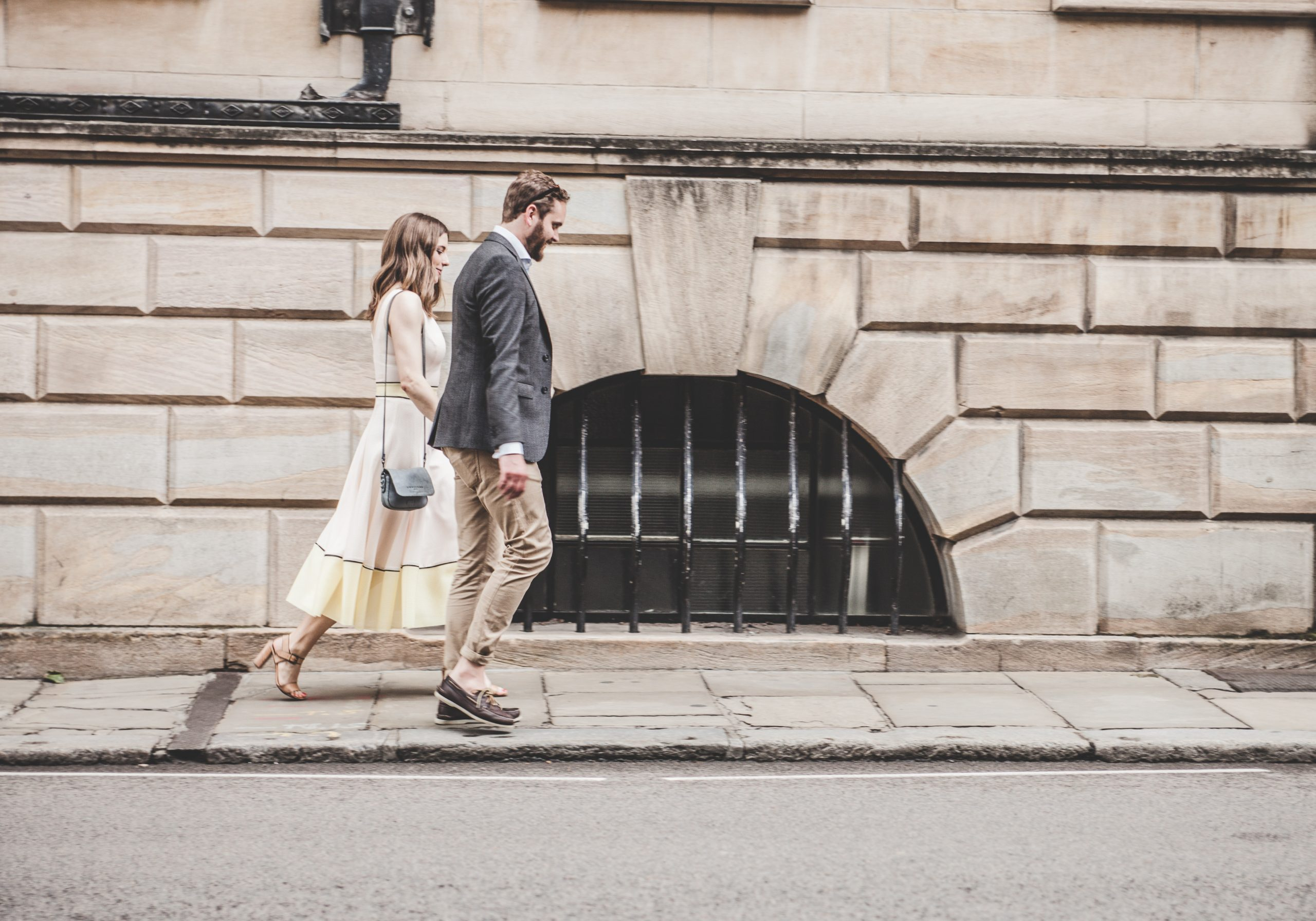 man and woman in formal clothes walking in city
