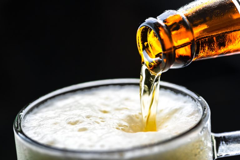 close up of beer being poured from bottle into glass