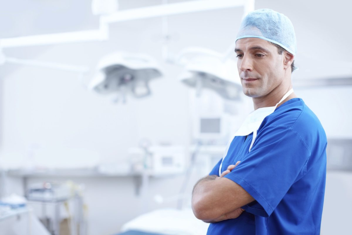male doctor with arms crossed in surgical suite
