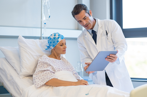 male doctor speaking with female cancer patient