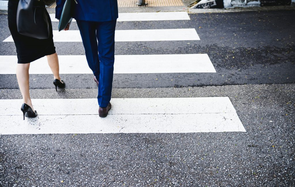close up of man and woman pedestrians in formal dress crossing crosswalk