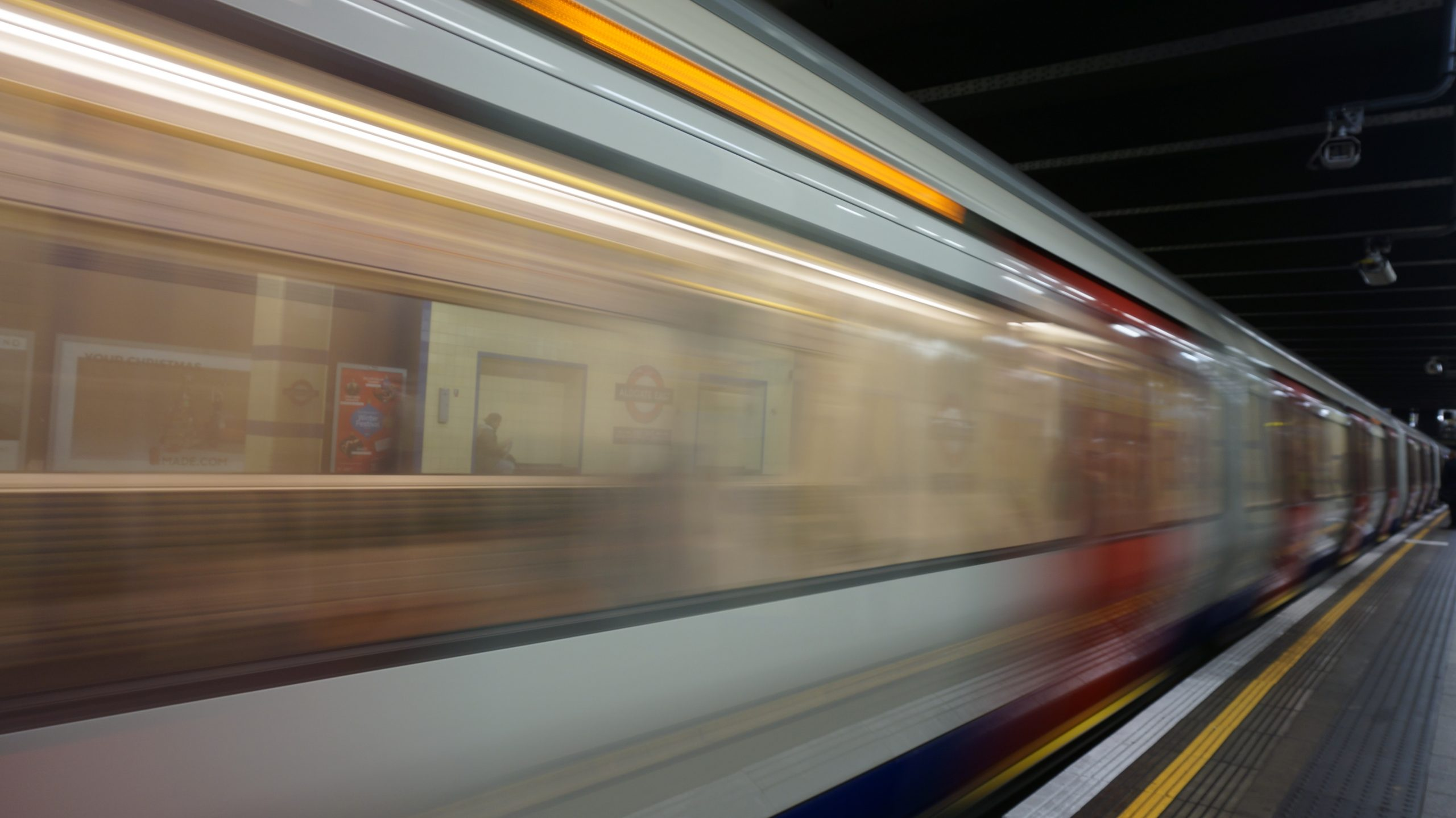blurred motion photo of subway train leaving station