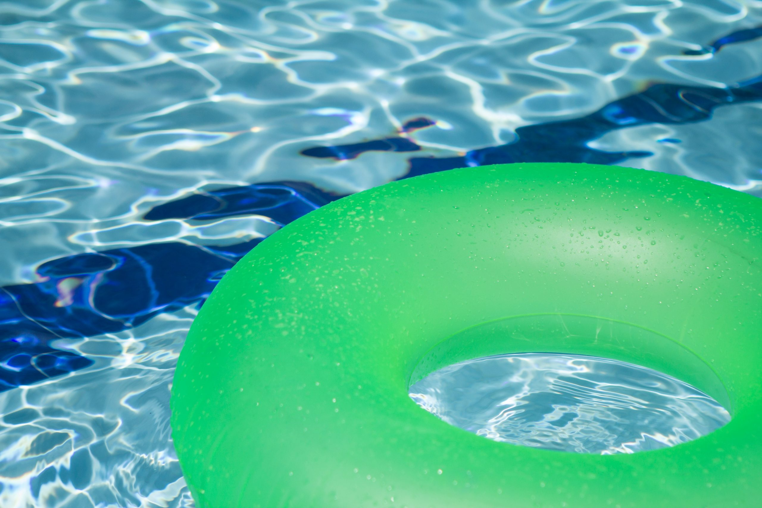 close up of green tube floating in swimming pool