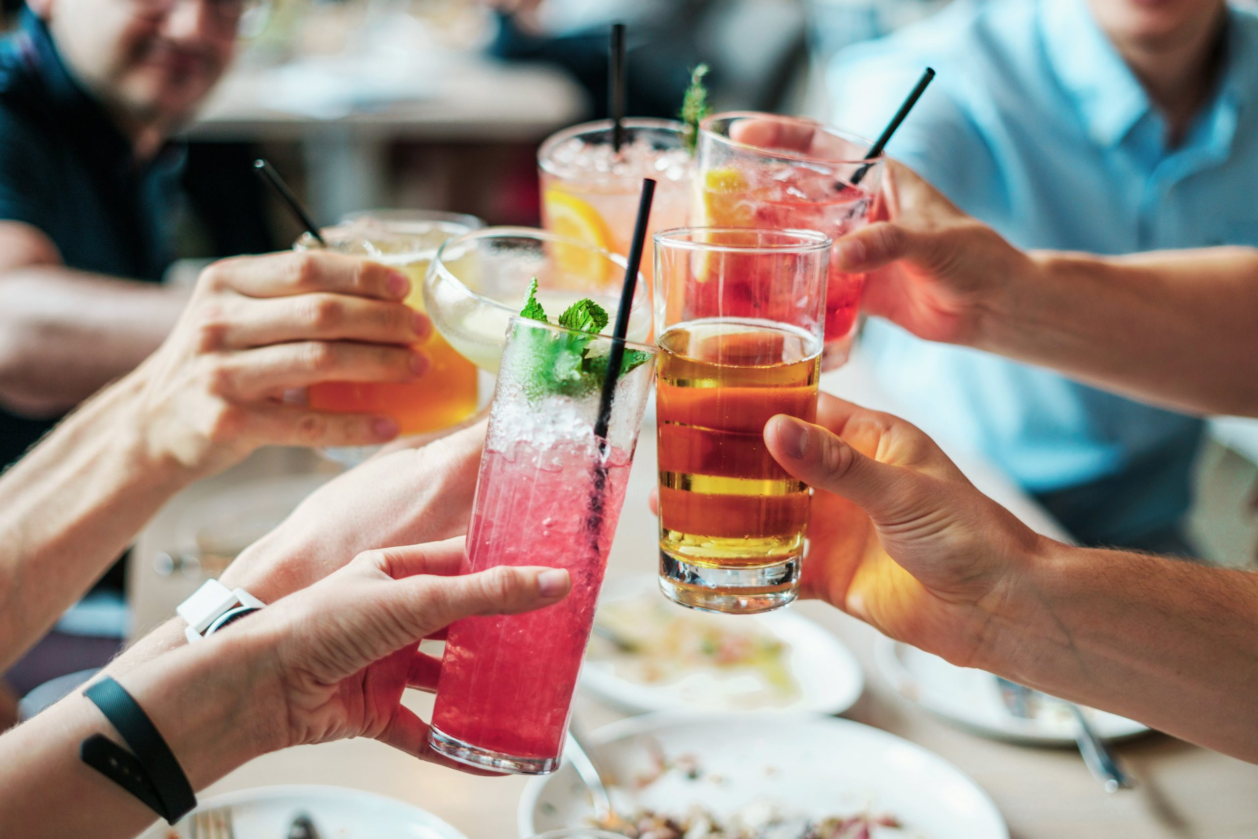 group of people doing cheers with alcoholic beverages