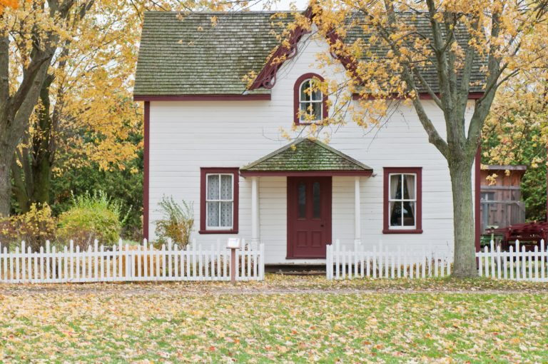 small quaint white house with red trim and picket fence