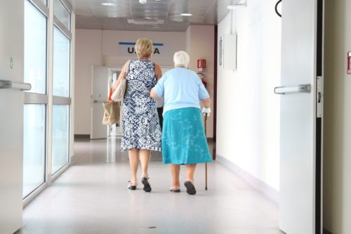 elderly woman walking with another woman helping her in a hospital hallway