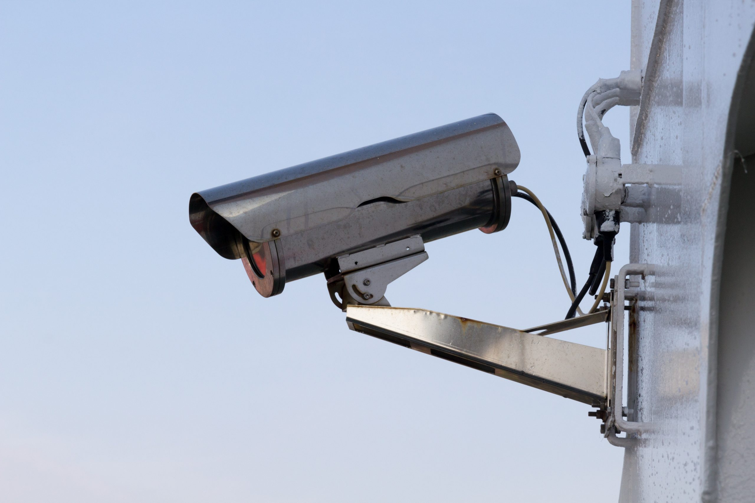 close up of silver security camera on metal structure