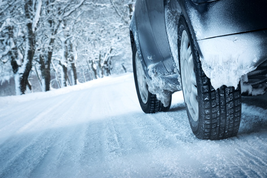close up of car tires driving on snowy winter road