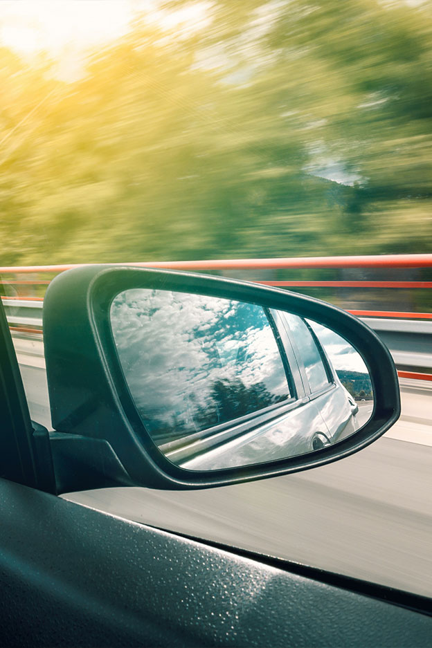view of car side mirror while car is driving