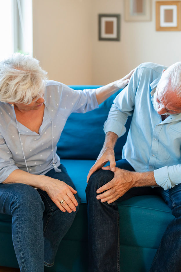 Elderly woman comforting old man with knee joint pain