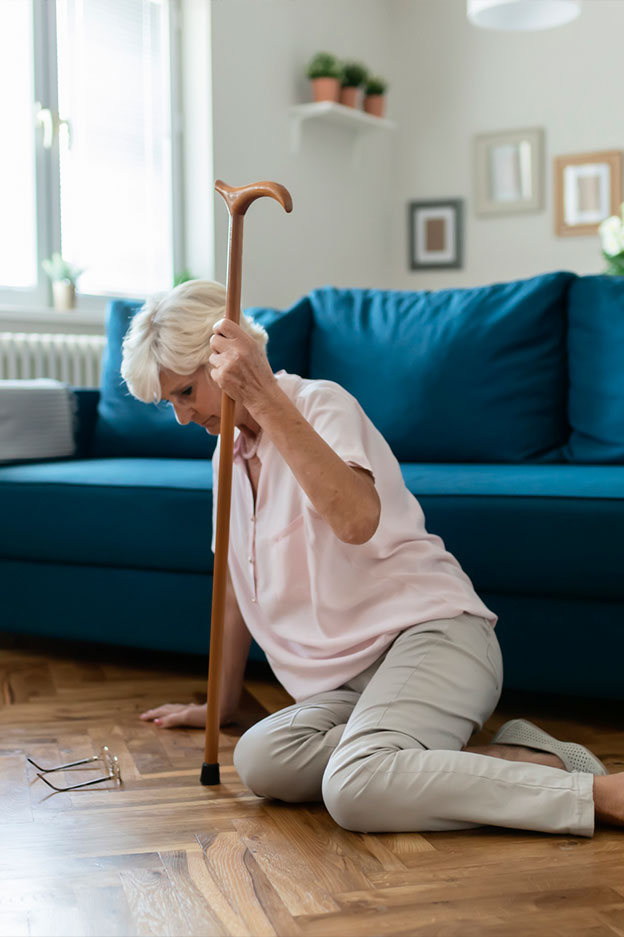 elderly woman with cane on floor after slip and fall accident