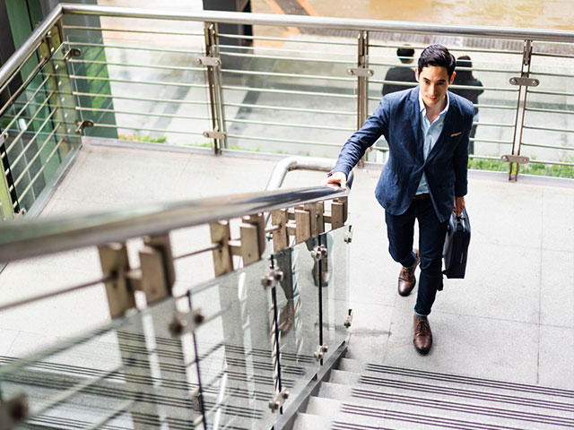 young man in business attire walking up stairs