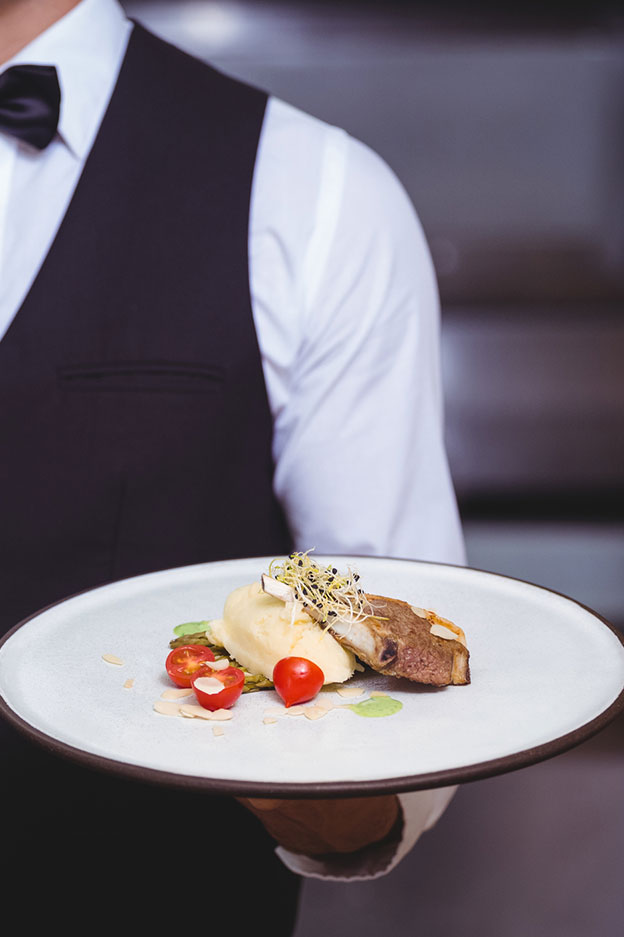 close up of waiter serving food in restaurant