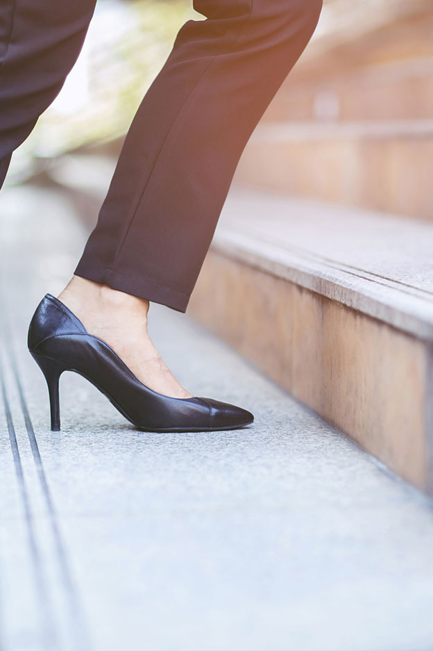 close up of foot of woman wearing heels climbing up stairs