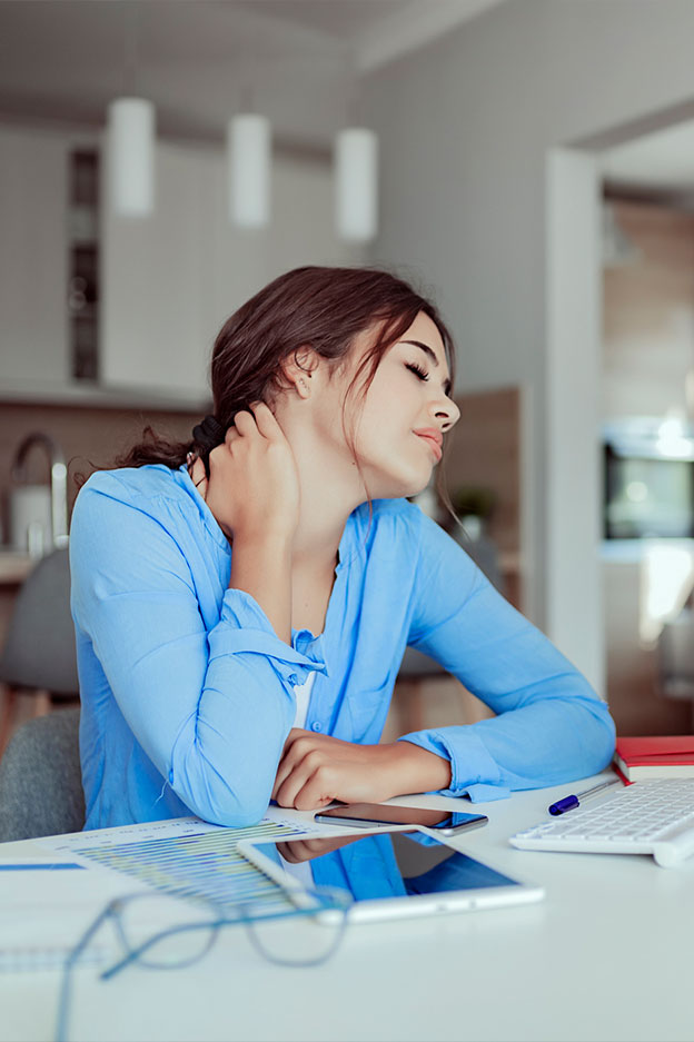 young woman seated at desk with back and neck pain after injury from accident