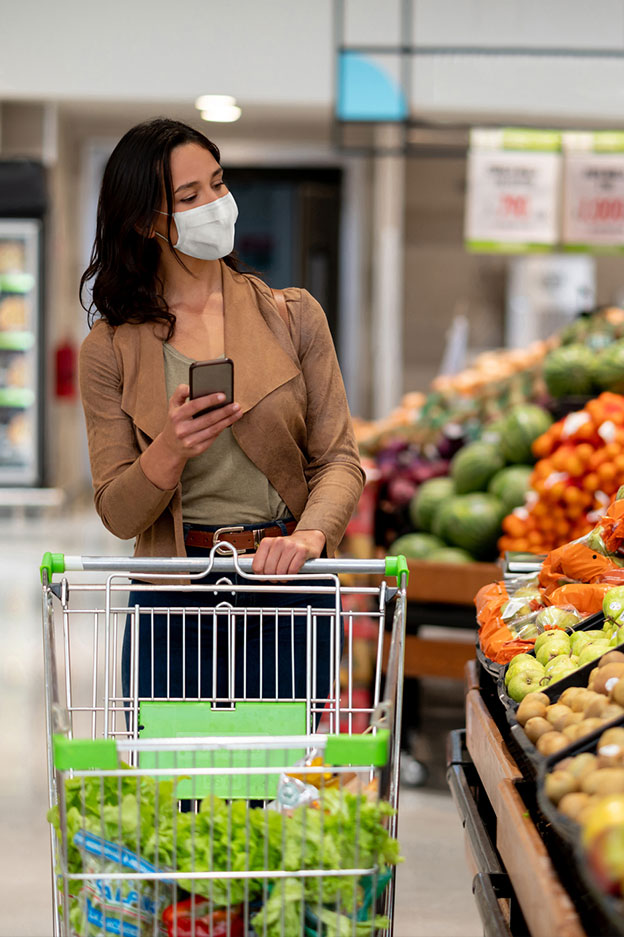 woman with mask grocery shopping in supermarket produce aisle