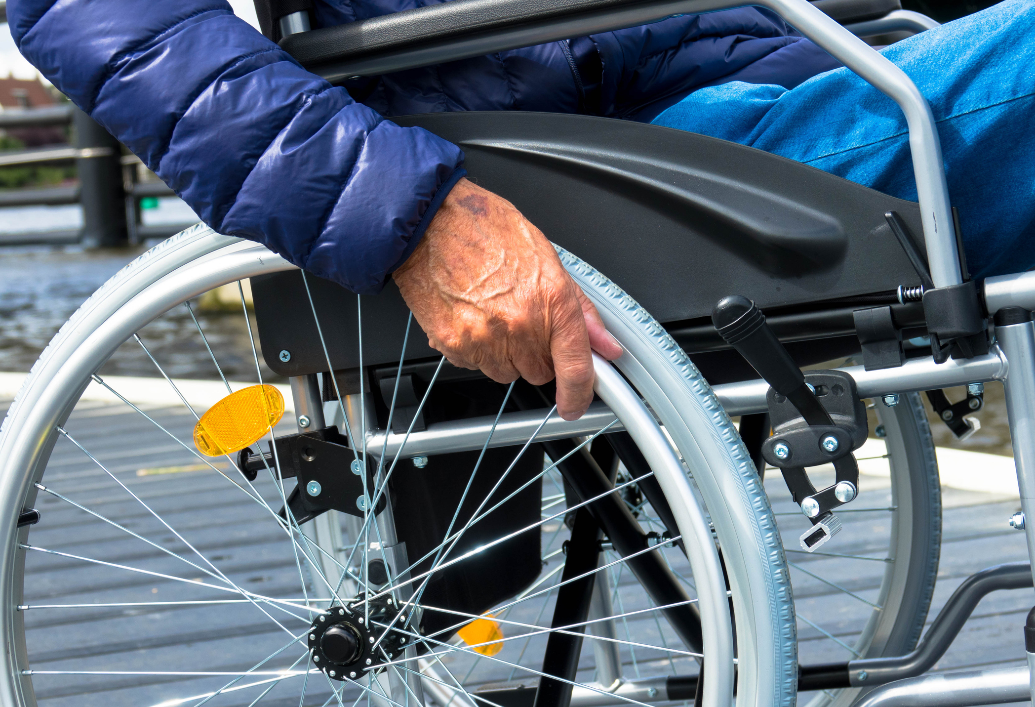 Close up of hands disabled senior sitting on wheelchair at outdoor