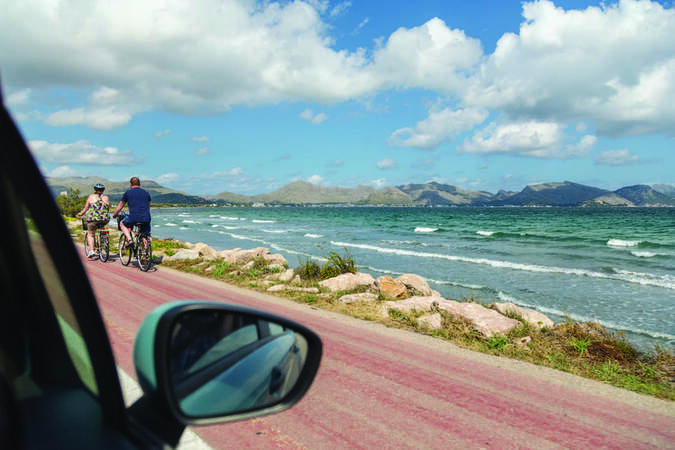 car side view with mirror driving along coast in summer