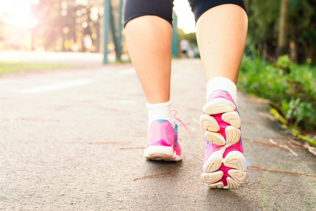 close up of woman's feet in pink sneakers walking on a trail